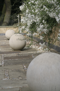 These stone balls on a roof terrace are uplit at night creating dramatic shadows