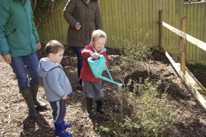 The children helping with the watering during planting
