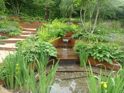 Corten steel used to terrace the garden and channel water to a pool below